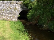 The arch of stone bridge crosses a stream